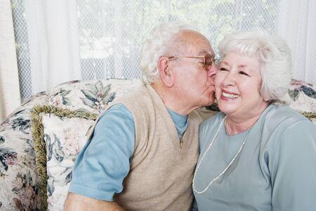 contented: Senior man kissing senior woman on cheek