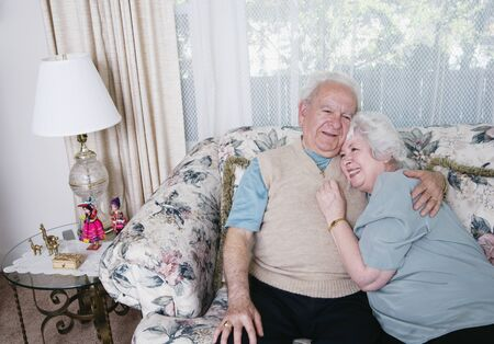 contented: Senior couple hugging on sofa LANG_EVOIMAGES