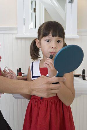 ni�os vistiendose: Chica joven que aplica el l�piz labial