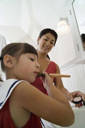ni�os vistiendose: Hija usando cepillo del maquillaje LANG_EVOIMAGES