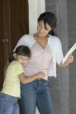 Mother and daughter standing in doorway