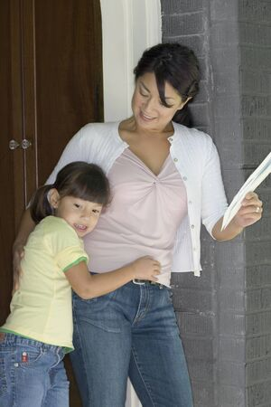 protect: Mother and daughter standing in doorway