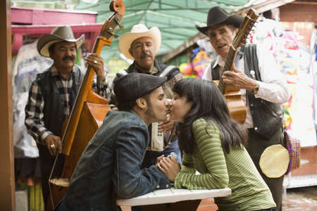 minority couple: Young couple with Mariachi band LANG_EVOIMAGES