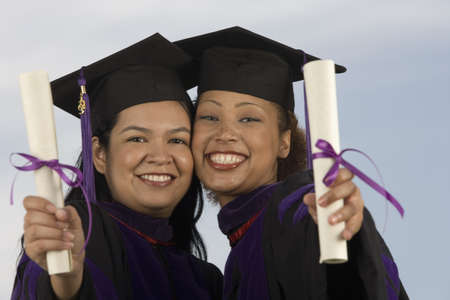 Two female graduates holding diplomas Stock Photo - 16071024