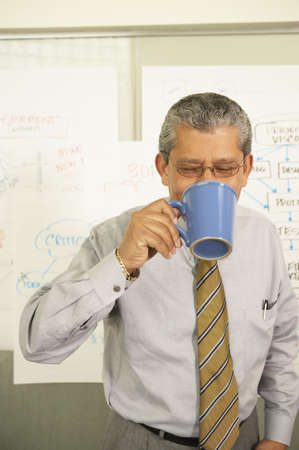 Businessman drinking from coffee cup Stock Photo - 16071031