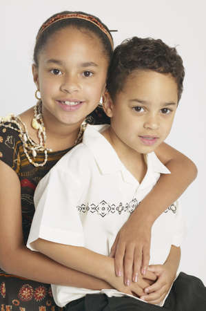 children's wear: Portrait of a young girl holding a young boy