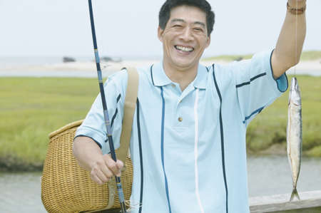 Portrait of a mature man holding a fishing rod with a fish Stock Photo - 16071030