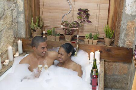 mujer bañandose: Joven pareja juntos en un baño de espuma brindando con champán