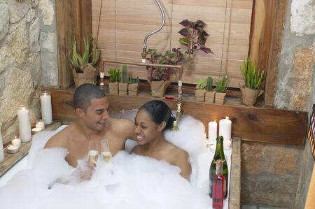bathing man: Young couple together in a bubble bath toasting with champagne