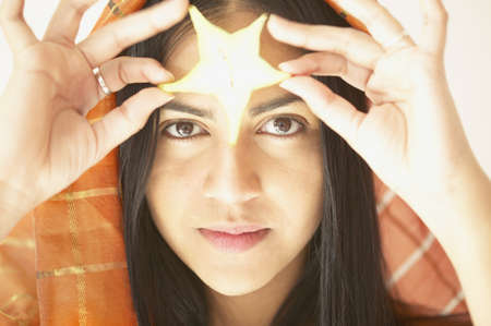 above 18: Young woman holding a star decoration