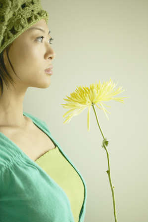 far away look: Portrait of a young woman holding a flower
