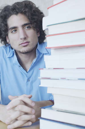 anticipate: Teenage boy looking at stack of books