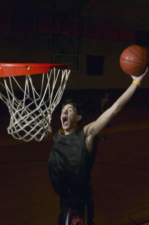 the height of a rim: Basketball player about to slam dunk the ball LANG_EVOIMAGES
