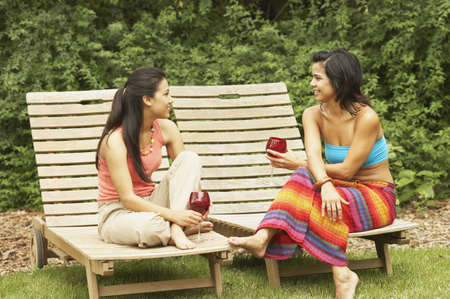 above 18: Two young women sitting outdoors LANG_EVOIMAGES