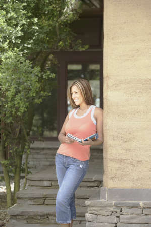 Young woman leaning against wall Stock Photo - 16071312