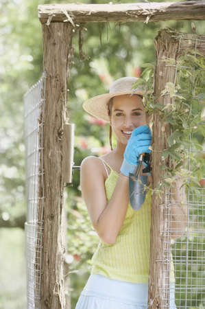 above 18: Young woman wearing gardening gloves
