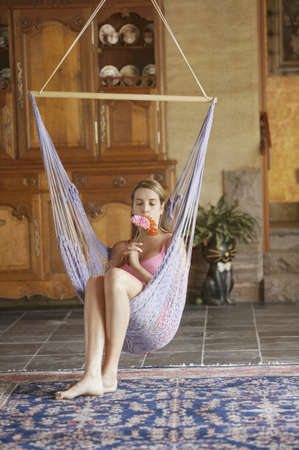 Young woman sitting on swing LANG_EVOIMAGES
