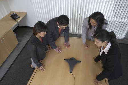 dressed for success: Business professionals using speaker phone LANG_EVOIMAGES