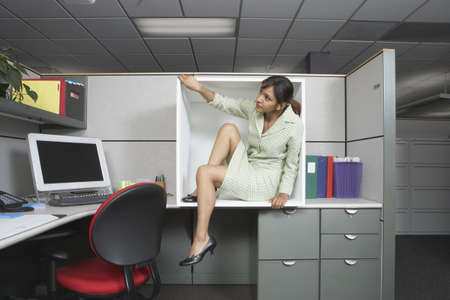 Businesswoman exiting office cubicle Stock Photo
