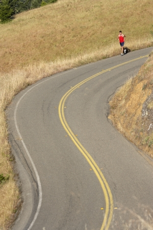 curve road: Male runner on winding rural road LANG_EVOIMAGES