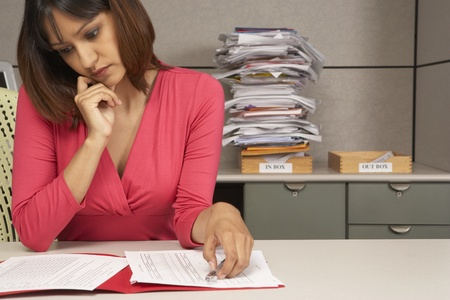 Businesswoman reviewing paperwork at desk Stock Photo - 16071377