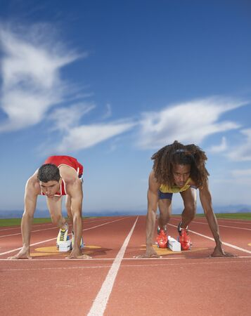 Male track runners prepare to race Stock Photo - 16071386