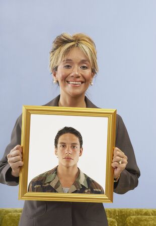 Proud mother holding picture of son Stock Photo - 16071393