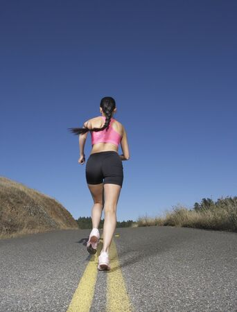 Woman running in the middle of the road Stock Photo - 16071408