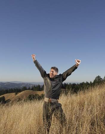 exclaim: Elated man standing in field LANG_EVOIMAGES