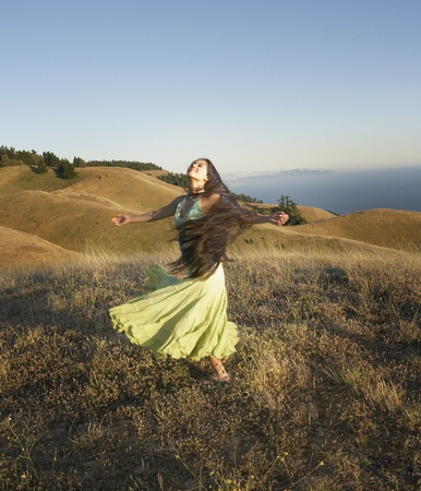 Passionate woman dancing on hillside Stock Photo - 16071420
