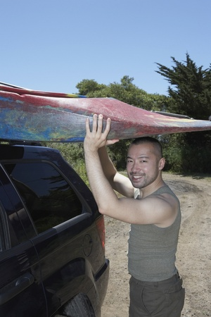 Man lifting kayak onto SUV roof Stock Photo - 16071429