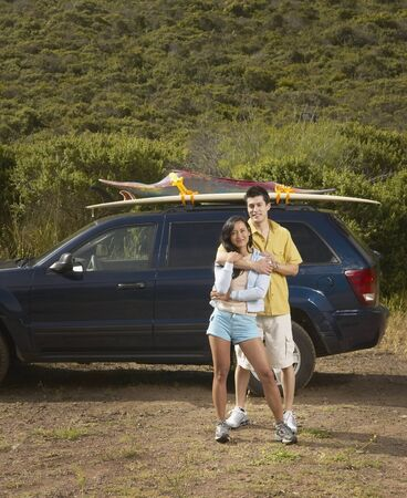 Couple standing alongside car on road trip Stock Photo - 16071431