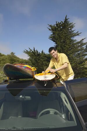 Man tying surfboard to car rack Stock Photo - 16071432