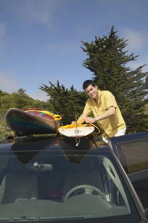Man tying surfboard to car rack Stock Photo - 16071432