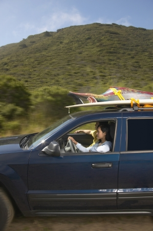 Couple driving SUV on road trip