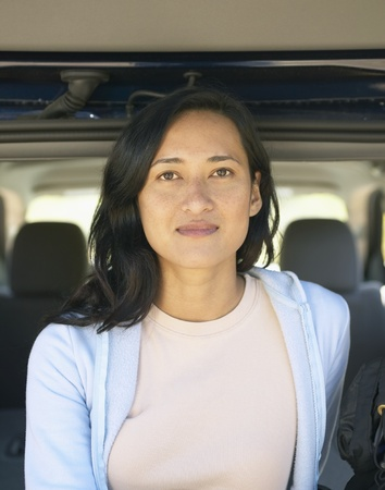 contentedness: Woman posing from inside SUV hatch LANG_EVOIMAGES