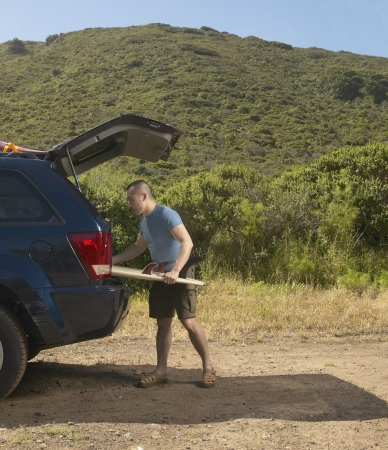 Man packing surfboard into SUV Stock Photo - 16071438