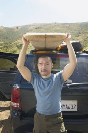 land locked: Man lifting surfboard from car rack LANG_EVOIMAGES