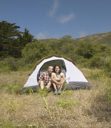 Couple posing outside their tent Stock Photo - 16071442