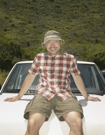 contentedness: Man resting on hood of his car