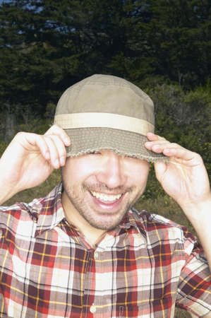 contentedness: Man pulling hat over his eyes