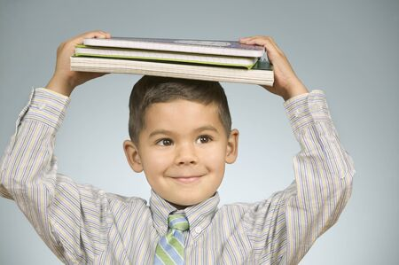 heap of role: Boy balancing notebooks on his head