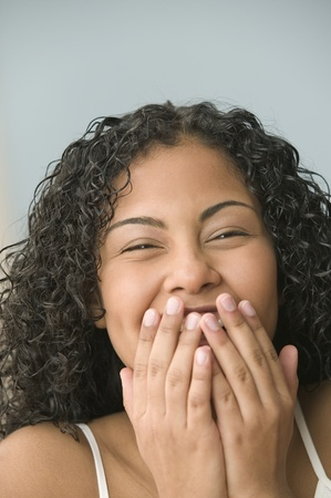 spunky: Teenage girl covering her mouth while laughing LANG_EVOIMAGES
