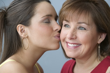 Teenage girl kissing her mother on the cheek 版權商用圖片