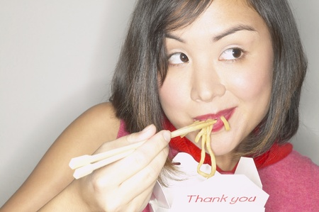 eating noodles: Young woman smiling eating noodles LANG_EVOIMAGES