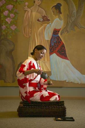 woman kneeling: Young woman kneeling pouring tea