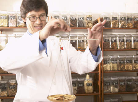 herbalist: Doctor measuring herbs on a weight scale LANG_EVOIMAGES