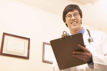 credentials: Portrait of a male doctor holding a clipboard