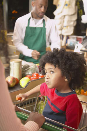 Sales clerk and a boy in a supermarket Stock Photo - 16071551