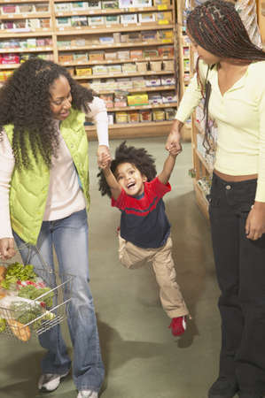 Mother shopping in a supermarket with her two children Stock Photo - 16071557